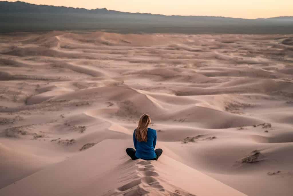 Mulher sentada de costas num deserto.