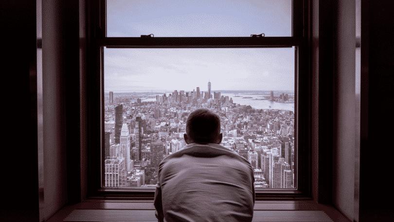 Figura de um homem olhando pela janela