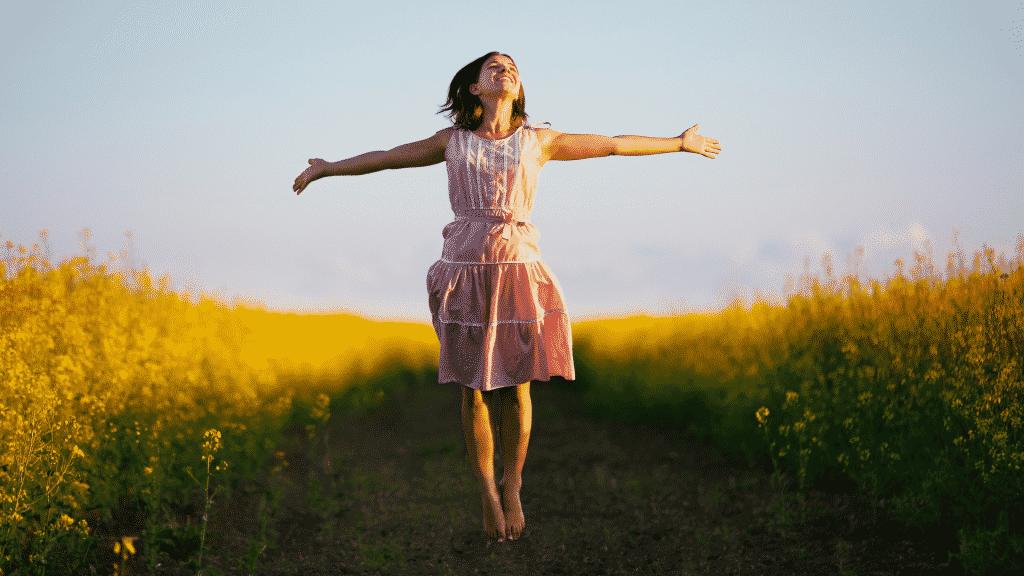 Mulher sorrindo de braços abertos enquanto pula em campo de flores