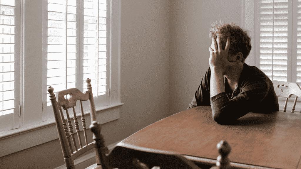 Homem sentado a mesa pensativo olhando para a janela