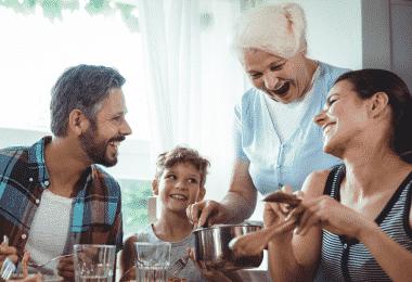 Família sorrindo e almoçando juntos na mesa