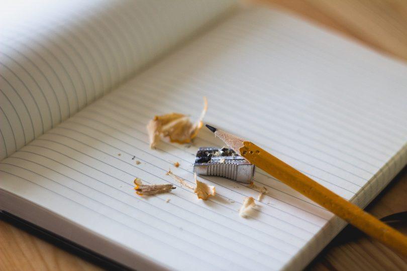 Imgem de um caderno aberto em uma mesa e sobre ele um lápis sendo apontado e ao lado o apontador.