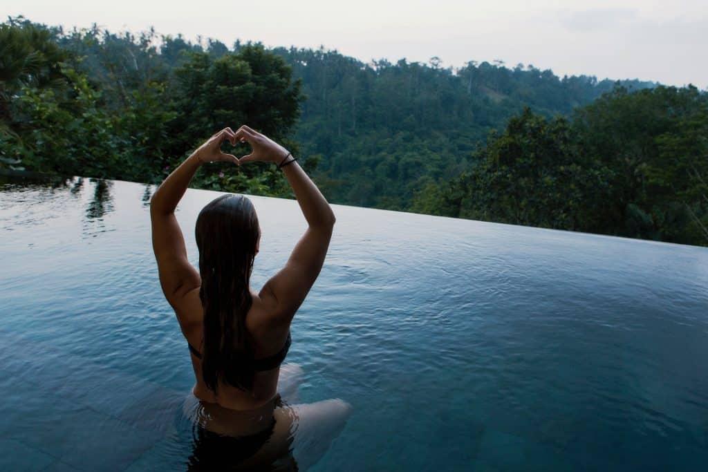 Imagem de uma mulher dentro de uma piscina de borda infinita. Ela está olhando para uma montanha. Está com os braços erguidos e com as mãos juntas, está formando a imagem de um coração.