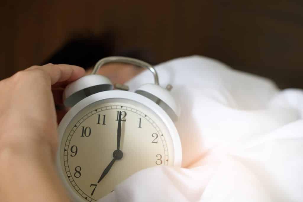 Mão tocando relógio despertador sobre cama branca.