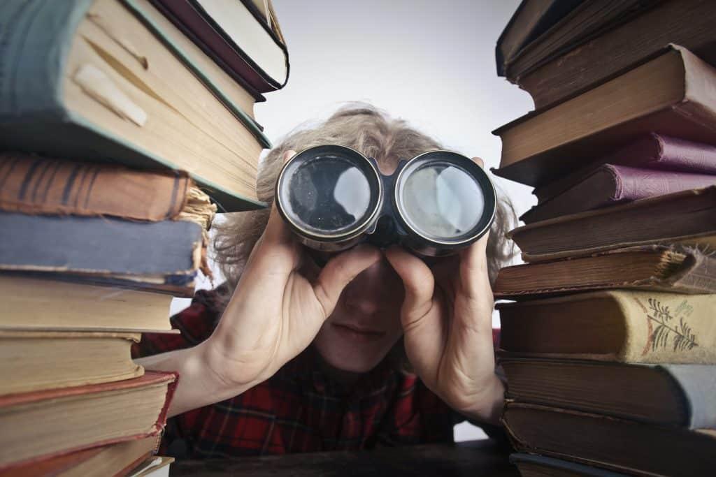 Menino olhando através de um binóculo cercado com pilhas de livros