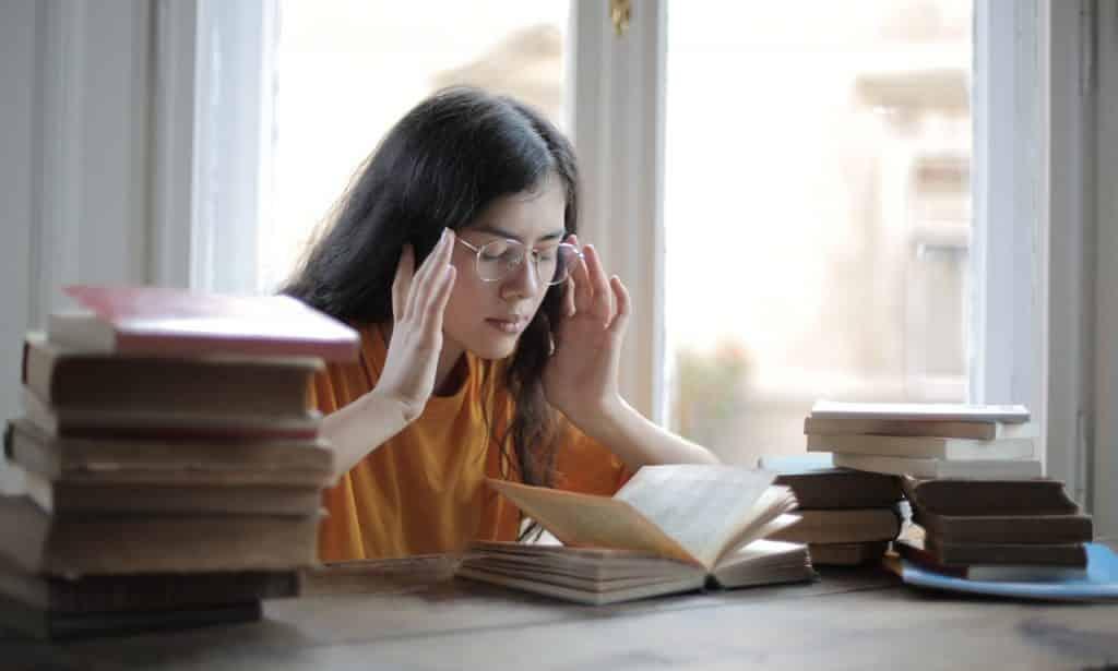 Menina com as mãos na cabeça de olhos fechados rodeada por livros