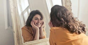 Mulher sorrindo vendo seu reflexo no espelho