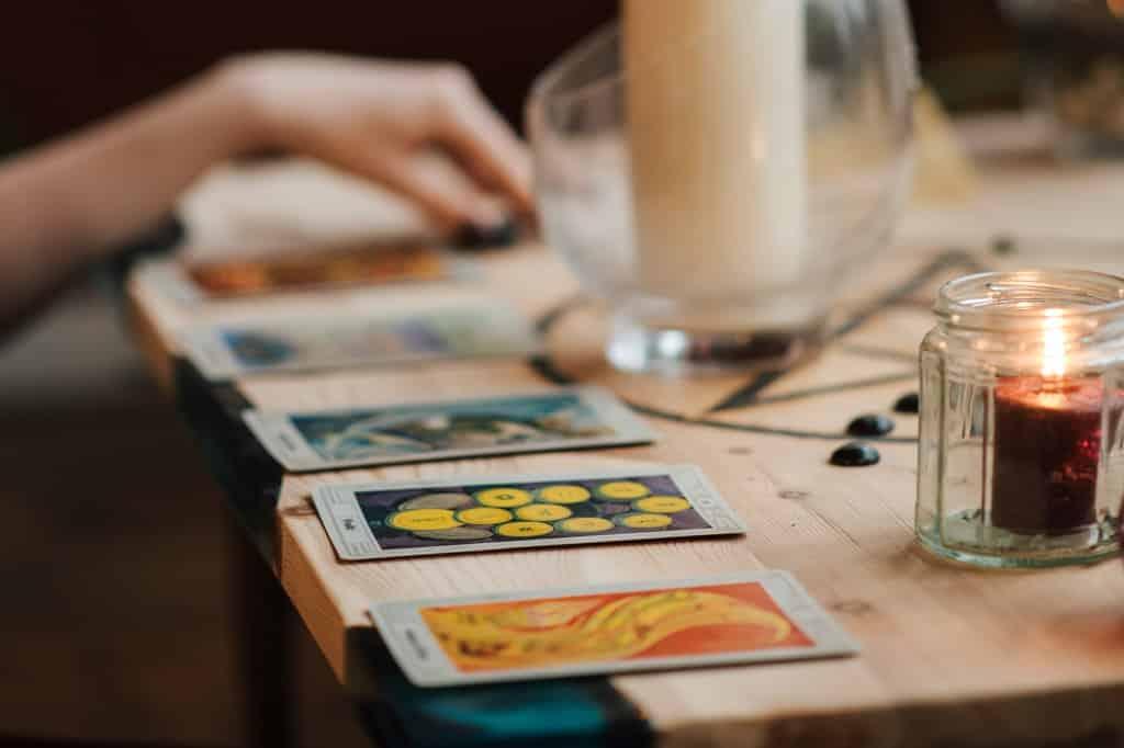 Cartas de tarot e velas sobre mesa de madeira.