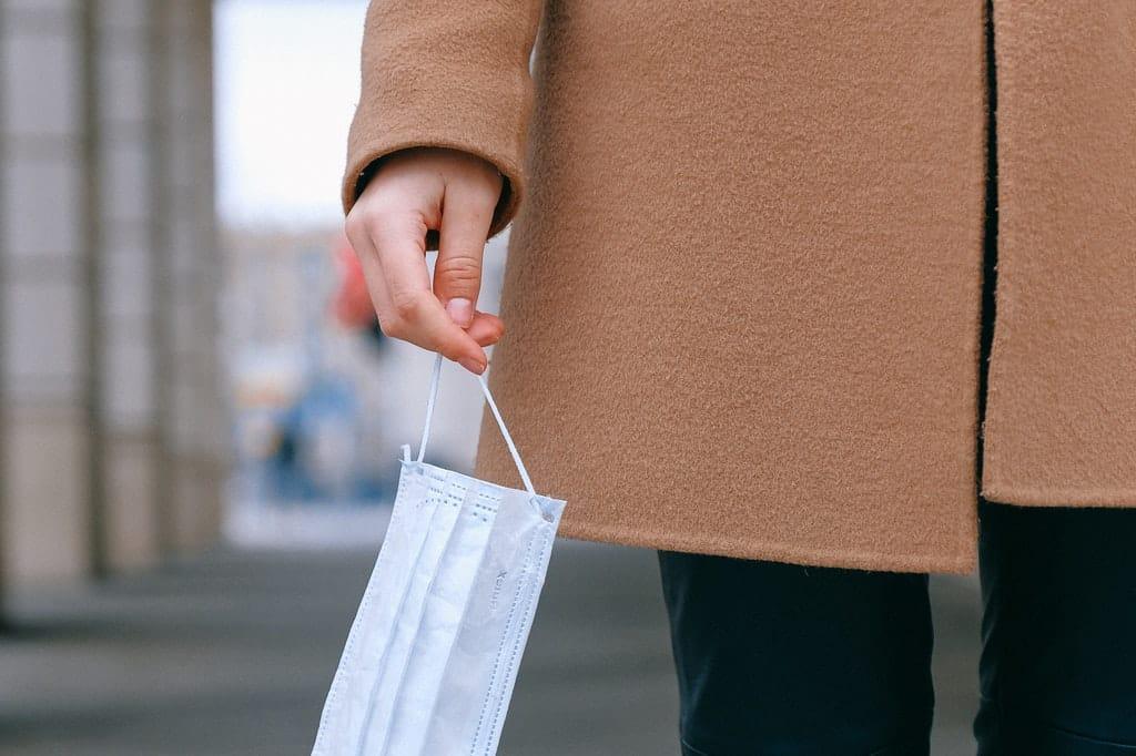 Mão segura alça de máscara branca e descartável.