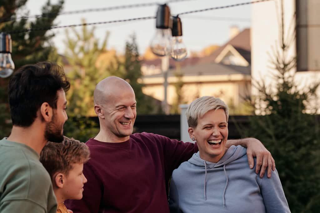 Homem e mulher abraçados enquanto sorriem; observando-os, há um rapaz adulto e um menino.