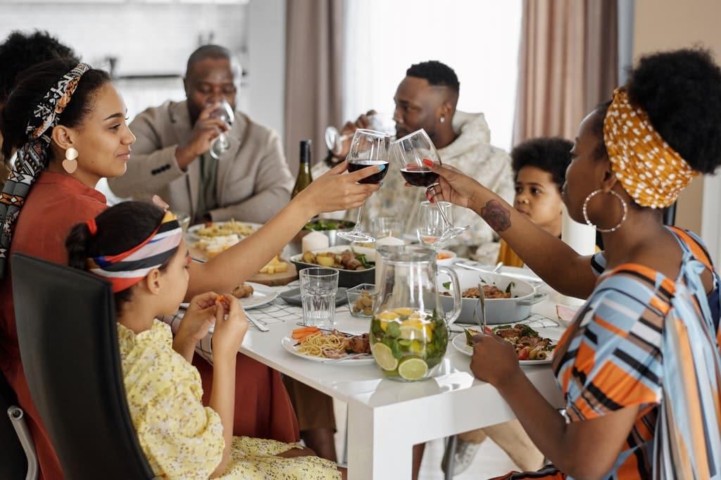 Família, composta por adultos e crianças, à mesa durante um jantar de Dia de Ação de Graças.