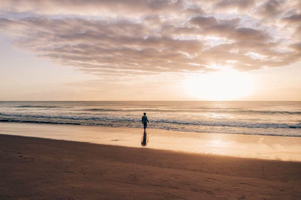 Silhueta masculina indo em direção ao mar.
