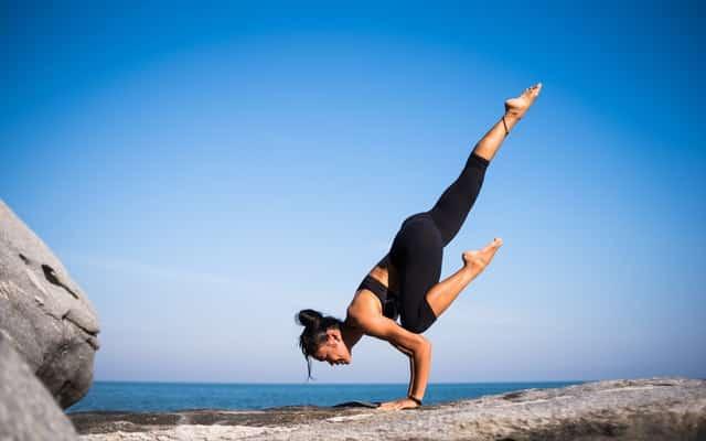 Mulher branca se equilibrando com as pernas levantadas.