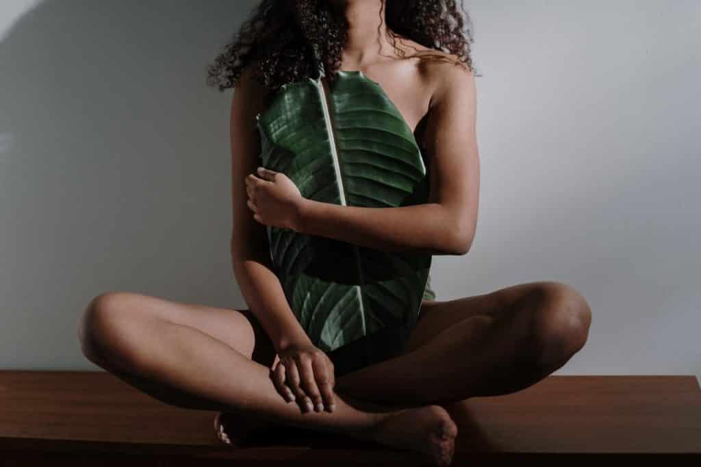 Mulher negra sentada no chão segurando folha em frente ao corpo.