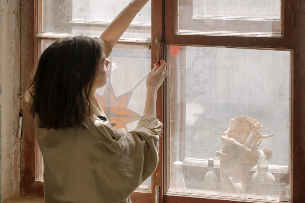 Mulher manipula o fecho de uma janela de vidro.