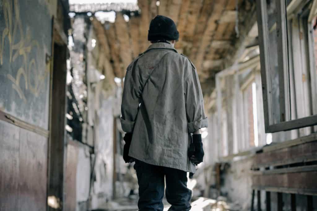 Menino de costas em uma casa totalmente destruída.