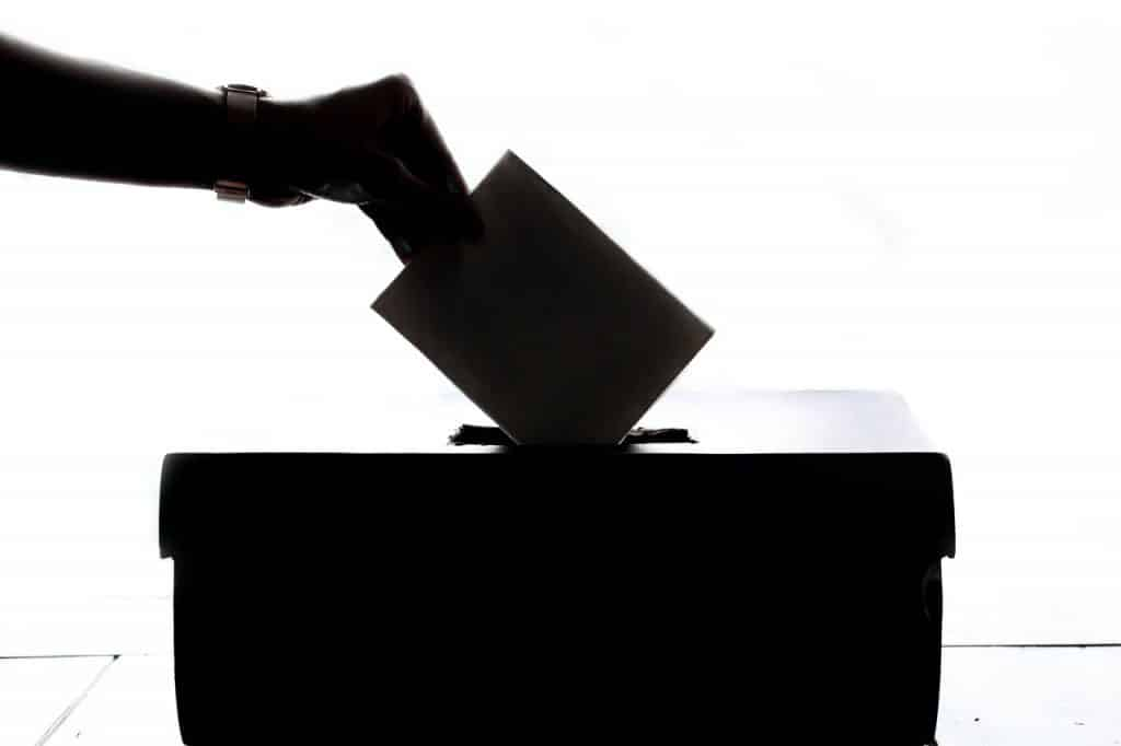 Mulher colocando cédula de voto em uma caixa.