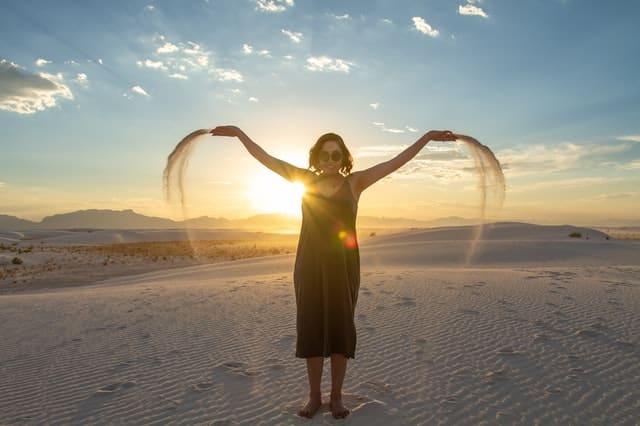 Mulher de braços abertos com areias nas mãos e sol e refletindo ao fundo