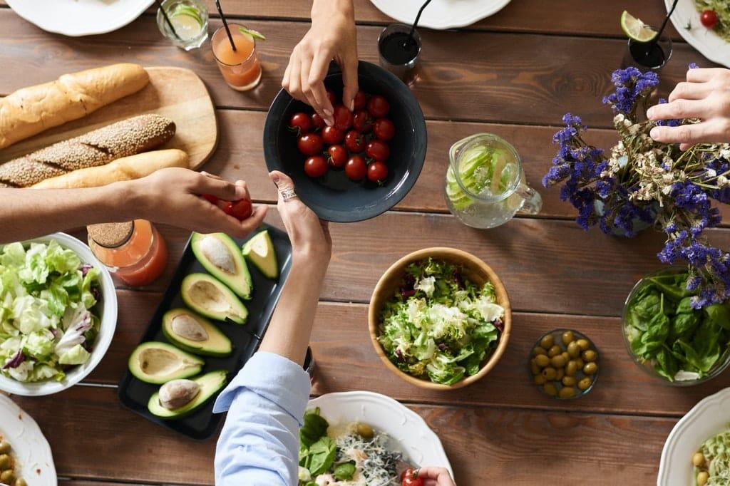 Mesa repleta de alimentos enquanto pessoas mexem neles.