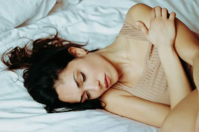 Mulher branca de cabelos castanhos deitada numa cama branca, com os braços ao entorno do corpo.
