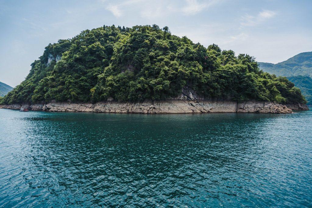 Ilha arbórea com mar ao redor.