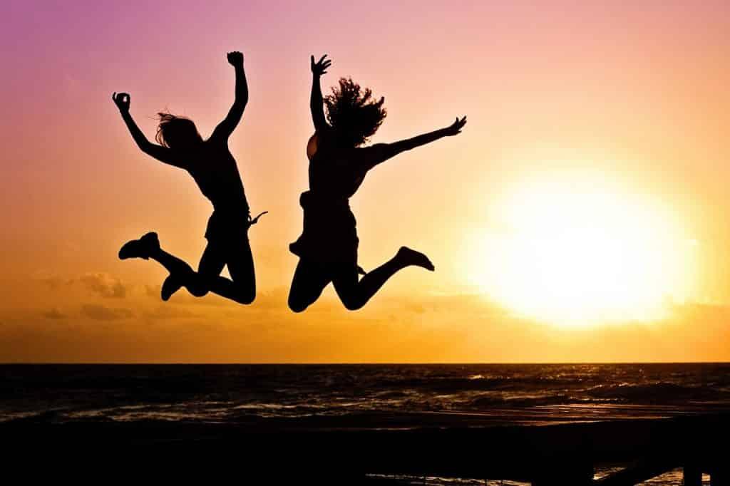 Silhuetas de duas pessoas pulando de alegria em um fim de tarde.