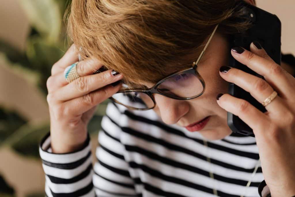 Mulher com uma das mãos na cabeça e a outra segurando o celular, ela está usando uma blusa listrada e óculos