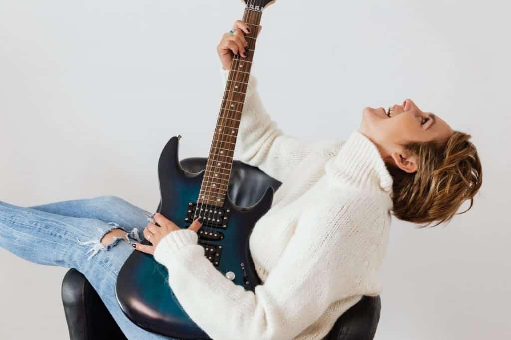 Mulher branca e loira de cabelos curtos, sentada numa poltrona preta, segurando guitarra enquanto olha para cima.