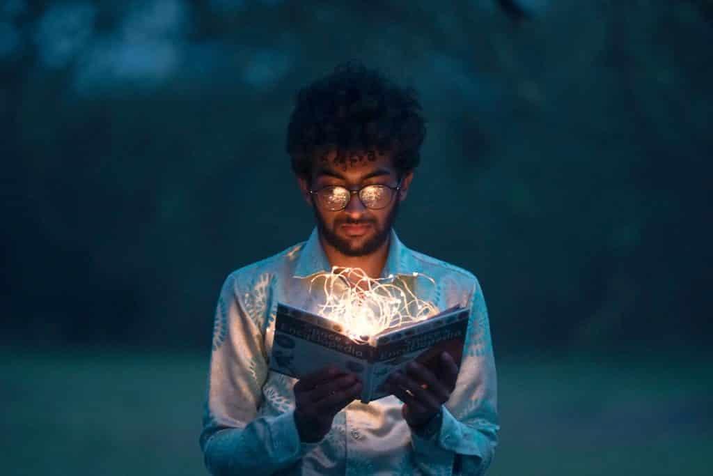 Homem lendo um livro com luzes saindo do livro representando o conhecimento