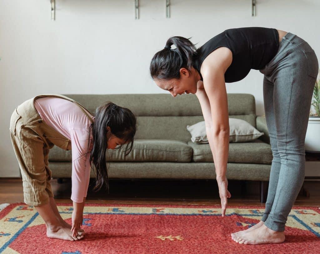 Mãe e filha alongando o corpo na sala de estar.