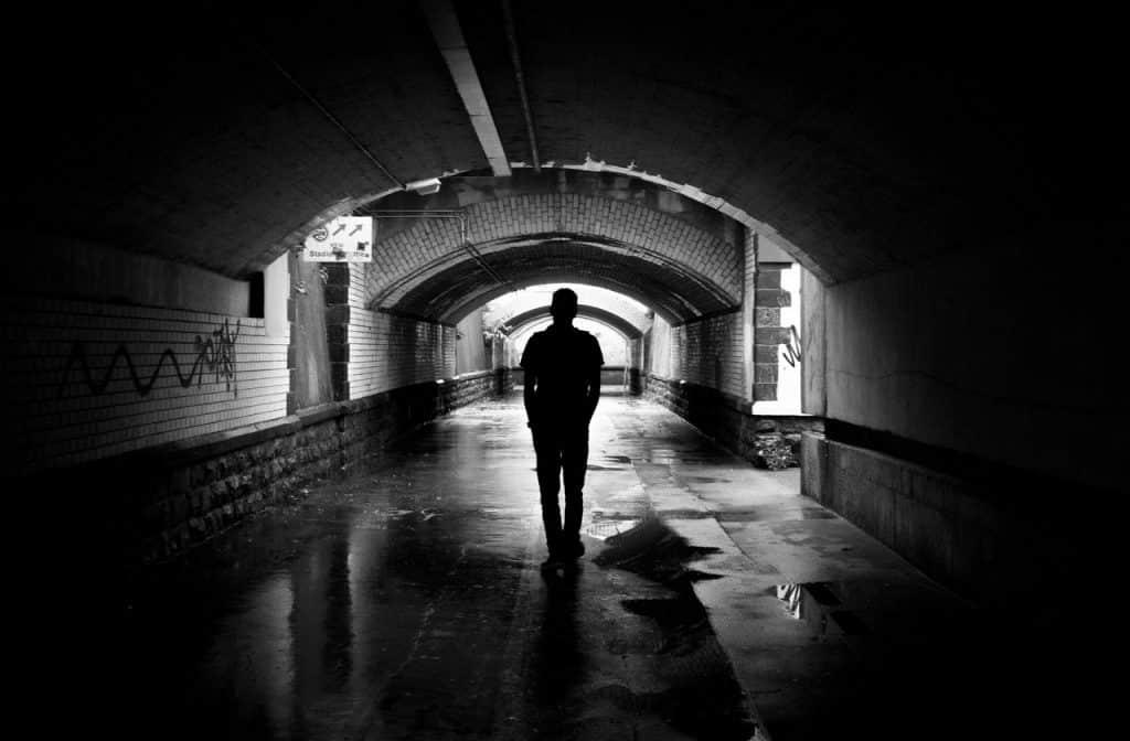 foto preto em branco de um homem andando em um túnel