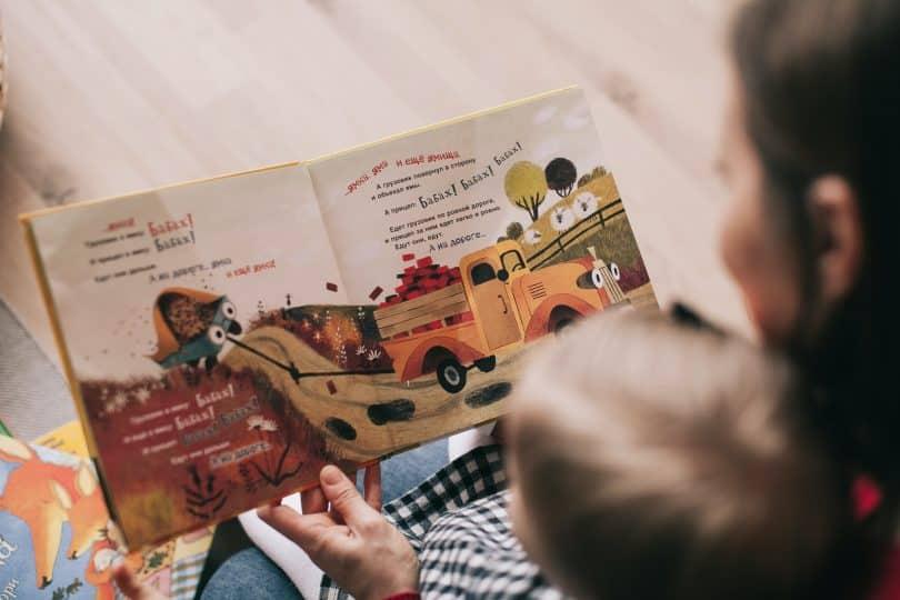 Mulher ao lado de uma criança com livro aberto