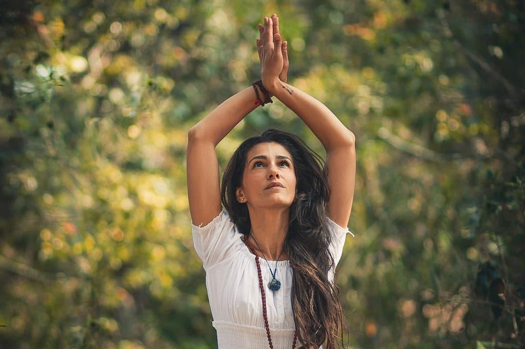 Mulher olha para cima, em direção às próprias mãos unidas acima de sua cabeça.