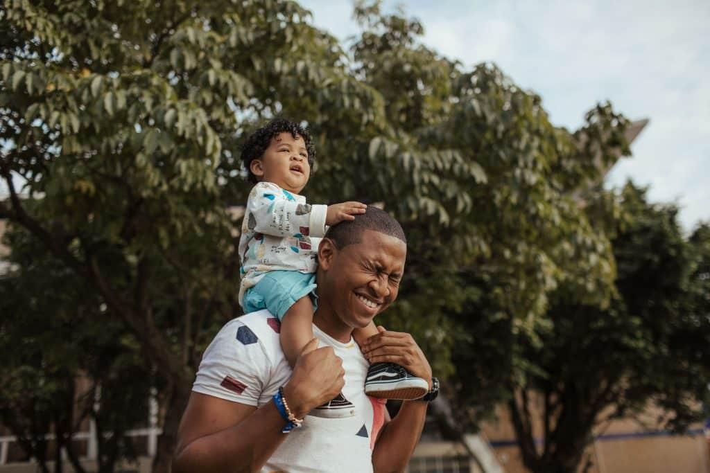 Bebê sentado no pescoço de um homem