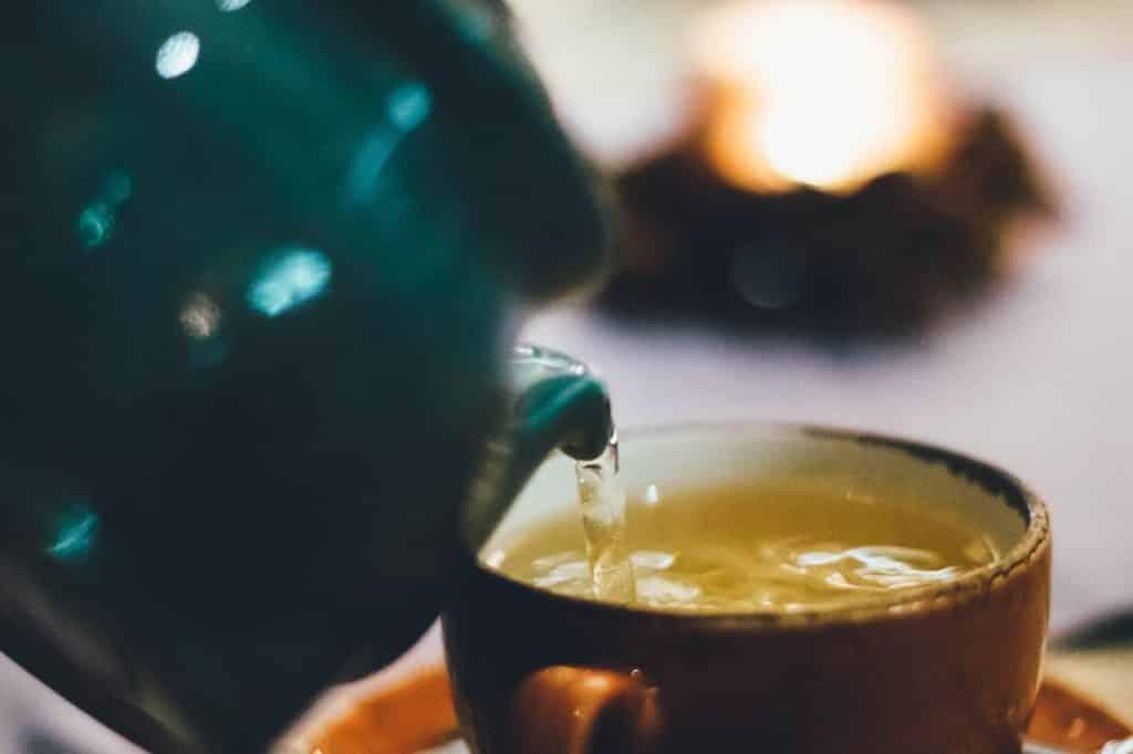 Xícara marrom com líquido amarelo sendo posto a partir de um bule azul.
