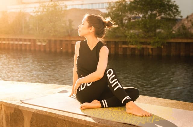 Mulher branca sentada na beira de um rio enquanto medita.