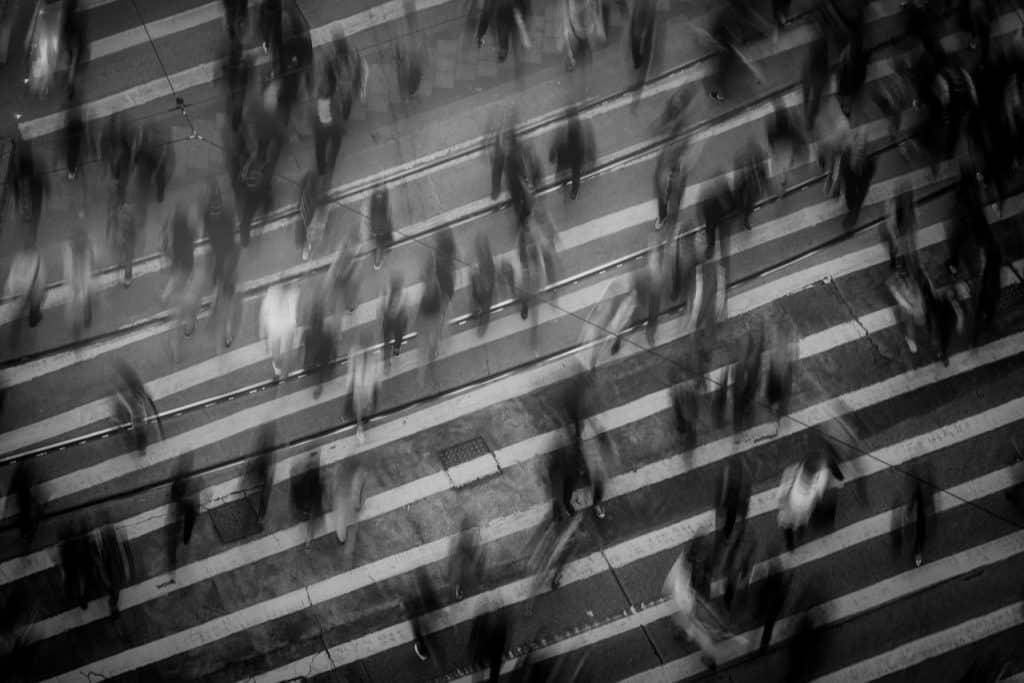 Vultos de pessoas atravessando uma rua.