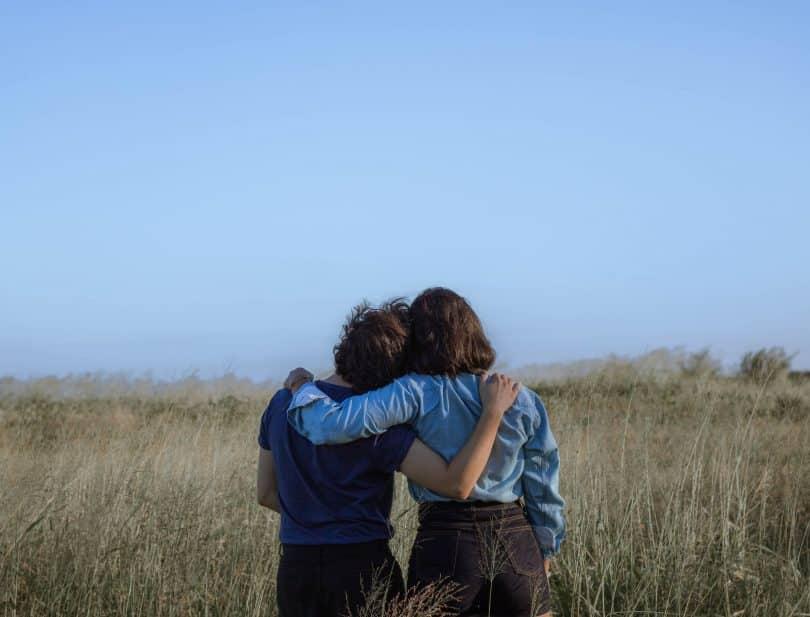 Duas pessoas abraçadas em um campo com gramado alto