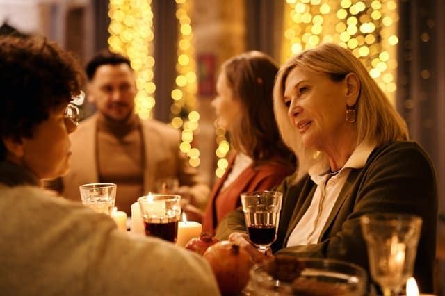 Senhora conversando em mesa de natal com família