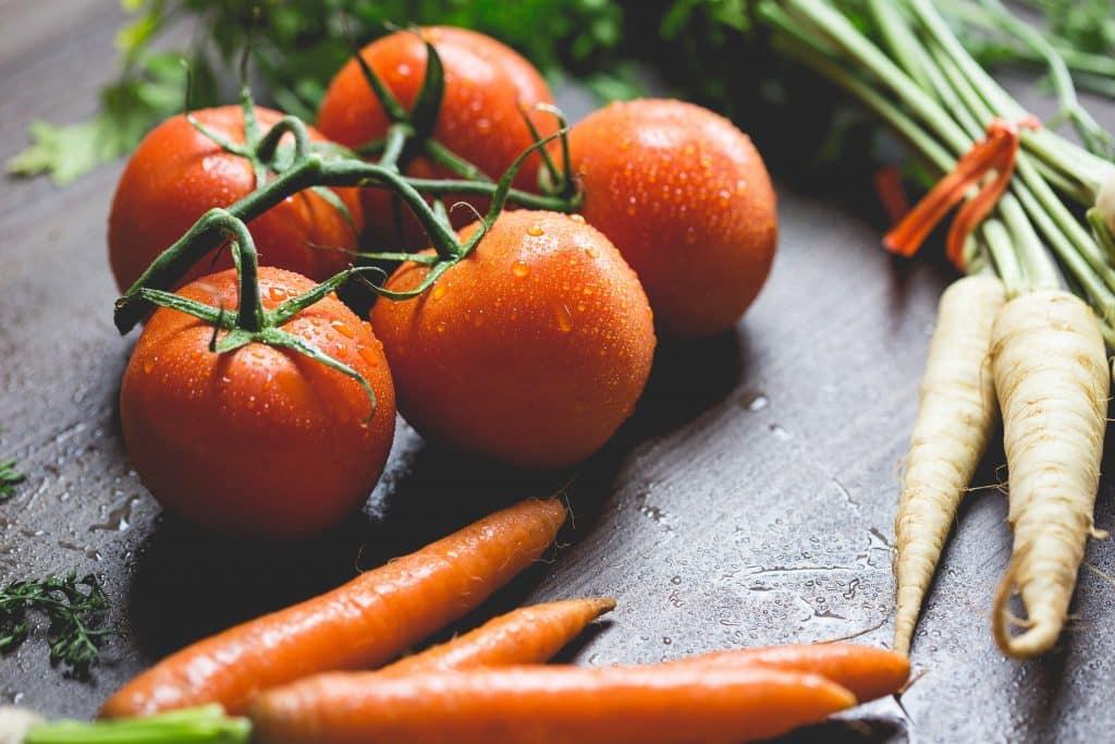 Cenouras, nabos e tomates molhados em uma mesa