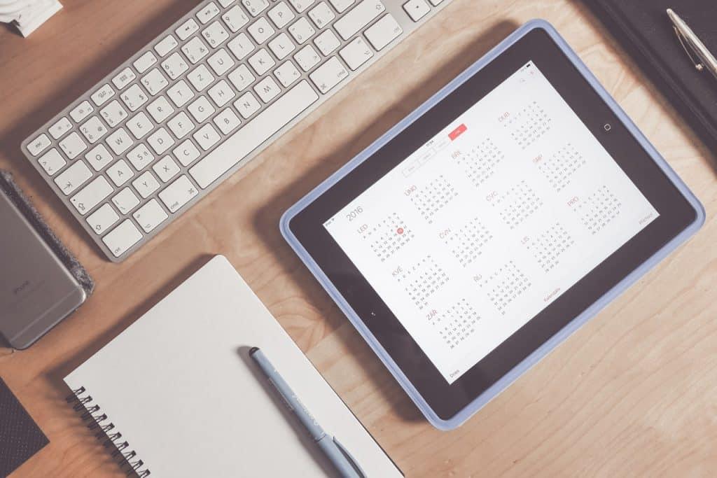 teclado de computador, um caderno e um calendário digital em cima de uma mesa