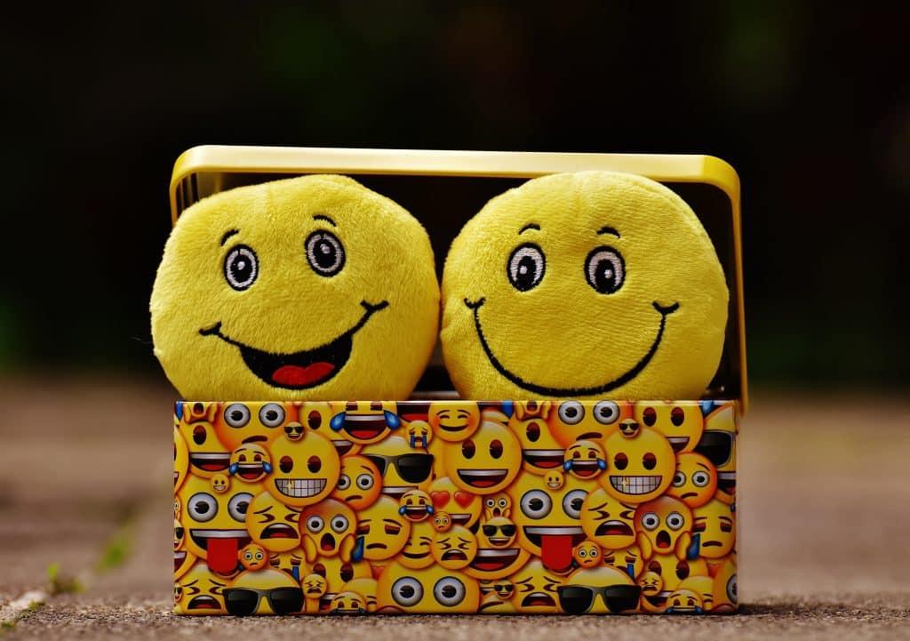 Dois emojis que representam emoções dentro de uma caixa colorida cheia de emojis menores