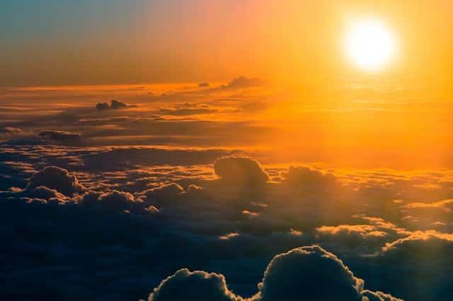 Céu visto acima das nuvens com sol refletindo