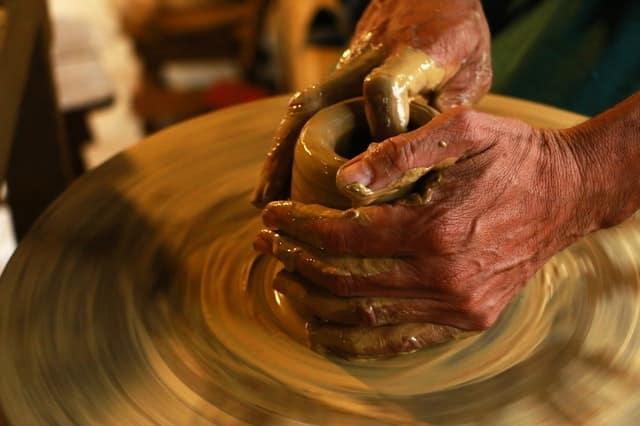 Mãos mexendo no barro em cerâmica