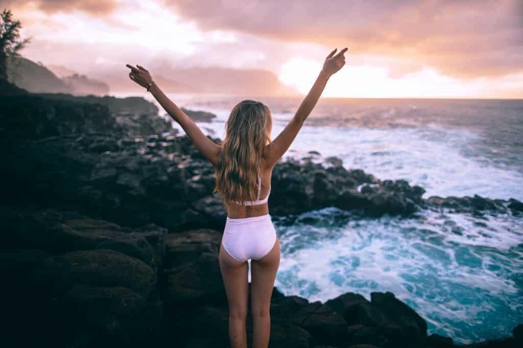 Mulher branca e loira de costas na praia.
