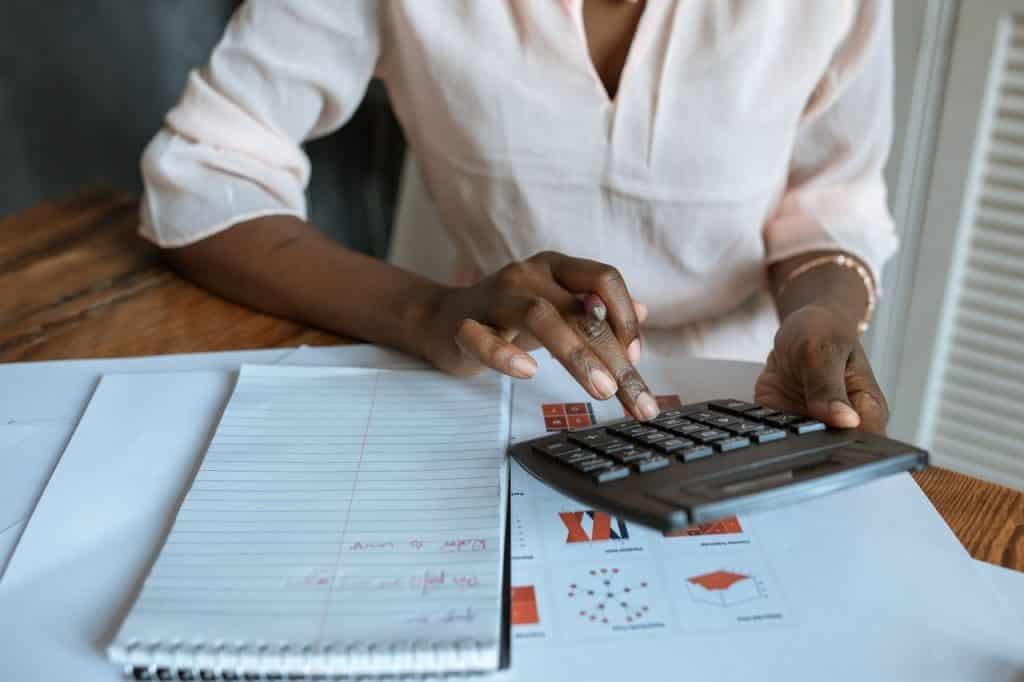 Mulher negra mexendo na calculadora com vários papéis sobre finanças em cima da mesa
