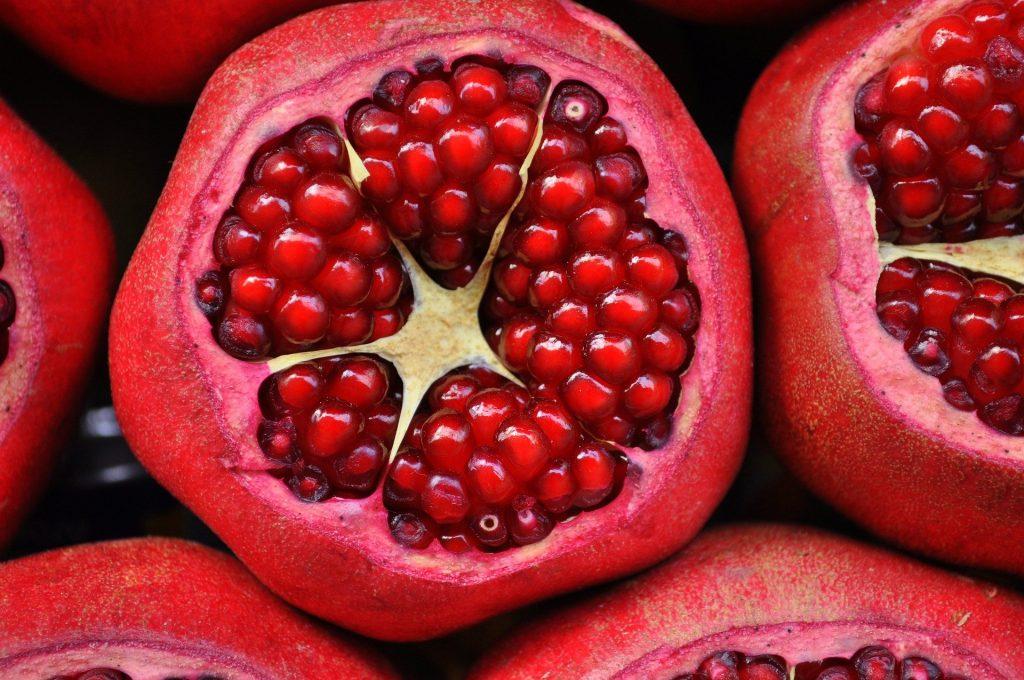 Imagem de várias romãs cortadas ao meio, suas sementinhas estão bem vermelhas.