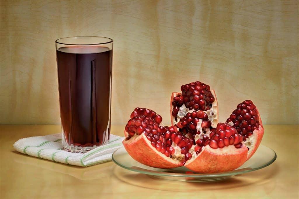 Imagem de um copo de suco detox feito com frutas vermelhas. Ao lado do copo, um pires contendo uma romã cortado em quatro partes iguais