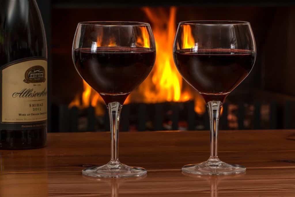 Imagem de duas taças contendo vinho tinto. Ao lado, uma garrafa de vinho.