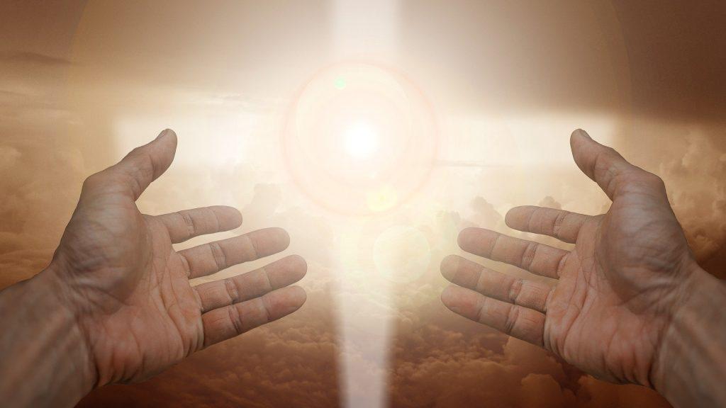 Imagem de duas mãos erguidas em direção à luz do sol. Ao fundo a imagem de uma cruz, representando a espiritualidade.